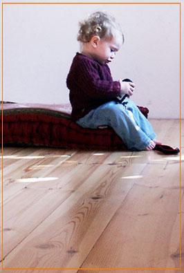 תינוקת יושבת על רצפה מחוממת